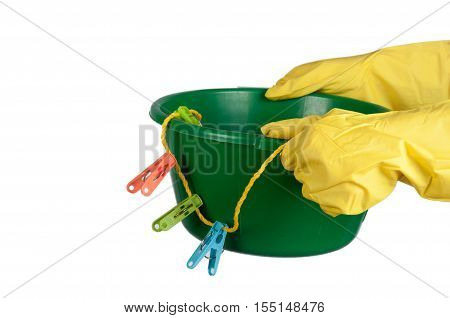Hands in yellow gloves hold washbowl with clothespins and clothesline. Isolated on white