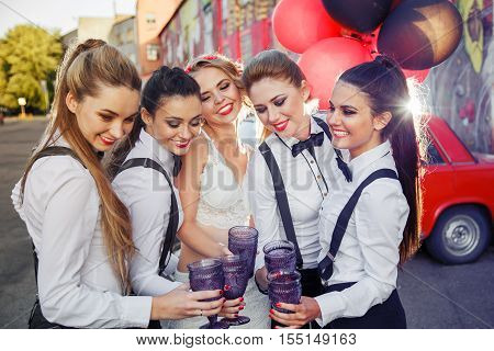 Beautiful happy girls celebrate a bachelorette party and drink champagne. Bridesmaids dresses in men's suits. The bride in a white sexy dress.
