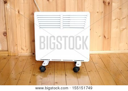 Working white electric convector heater plugged to timer power socket operated in smart house system against wooden wall inside room vertical front view photo closeup