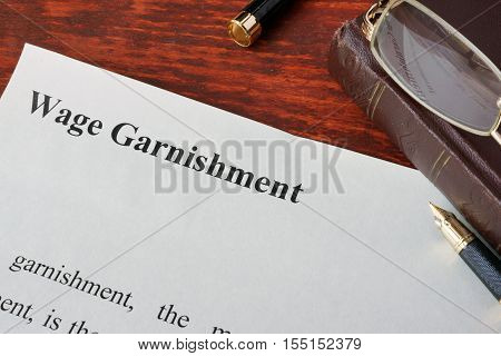 Wage Garnishment definition written on a paper. poster
