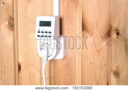Working white electric timer socket plug operated smart house system against wooden wall inside room side view closeup