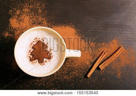 Cup of coffee with fir tree pattern of cinnamon on dark background