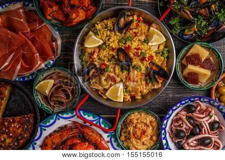 Typical spanish tapas concept. Concept include slices jamon bowls with olives anchovies spicy potatoes mashed chickpeas shrimp calamari manchego with quince marmalade pans with tortilla paella mussels on a wooden table. poster