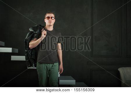 Studio Photography Young Brutal Guy. Man In Sunglasses, T-shirt, Jeans Keeps Black Leather Jacket, S