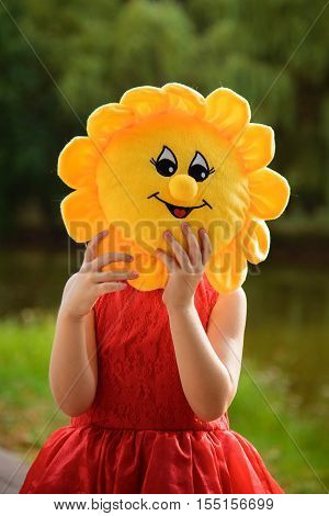 Little girl in a red dress standing in the park and covers her face with a soft toy in the form of the sun. Bright warm summer