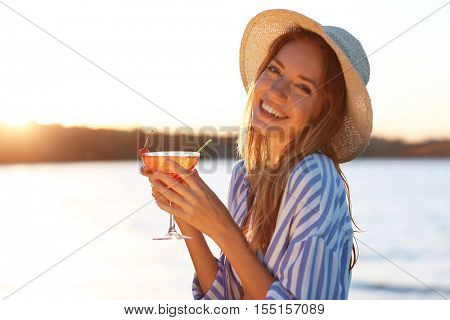 Portrait of beautiful young woman with margarita cocktail on blurred background