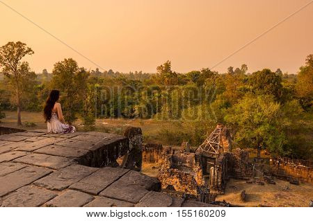 ANGKOR WAT CAMBODIA - JANUARY 28 2015: Young beautiful woman watching sunset at the top of Phnom Bakheng at Angkor Cambodia