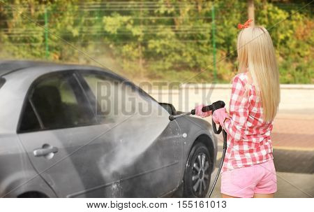 Woman washing car with high pressure water