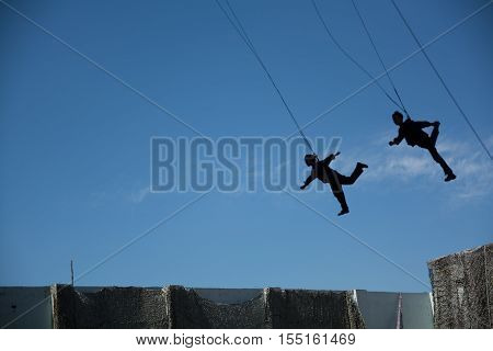 Men and women flying in sky with safety rope. Stunt people who fly on sky background.