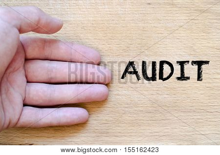 Human hand over wooden background and audit text concept
