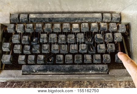 Old typewriter with special buttons LOVE word and hand of man push enter