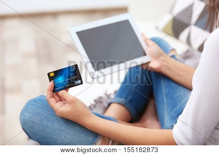 Woman with credit card and tablet making online shopping