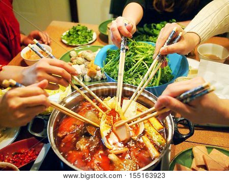 People is cooking with Chinese hotpot with chopsticks.