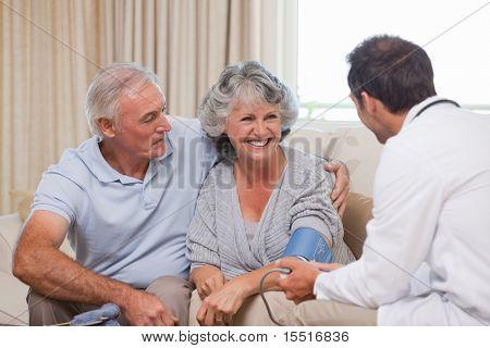 Arzt unter den Blutdruck von Patienten