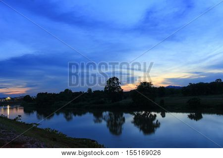 sunset sky colorful silhouette river twilight and woodland in nature early evening