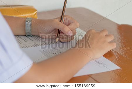 students writing a test in their exercise exam multi-choice in classroom