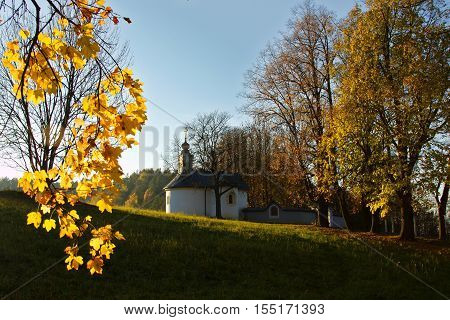 Calvary in Slovakia. Christian church in Banska Bystrica. Falling leafs in autumn landscape, Catholic chapel with cross symbol.