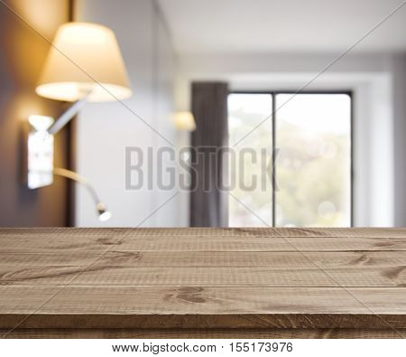 Empty wooden table on defocused simple hotel room interior background