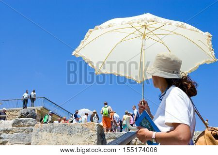 Crete Greece - June 14 2006: A tourist guide with umbrella in the archaeological site of the Knosso palace