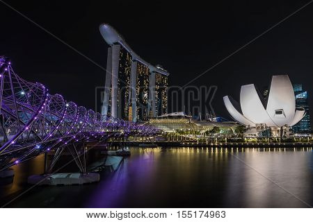 SINGAPORE - 1 OCTOBER 2016: View of Singapore skyline at night with Helix bridge, Hotel Marina Bay Sands and art science museum