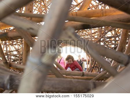 5th of November 2016 Bondi Beach Sydney Australia. Little girl climbing into an interactive sculpture titled The Golden hour by Cave Urban at Sculpture by the Sea