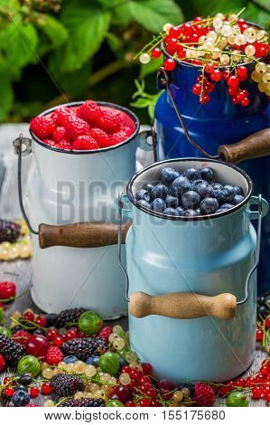 Fresh berry fruits in churn on old wooden table