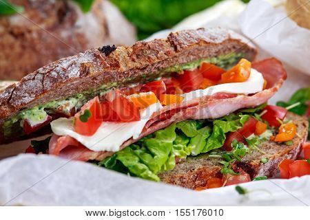 Fresh BLT Sandwich with Bacon Lettuce Tomato and Mozzarella on crumpled paper.