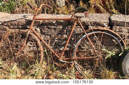 en cykel som står lutad mot en stenmur