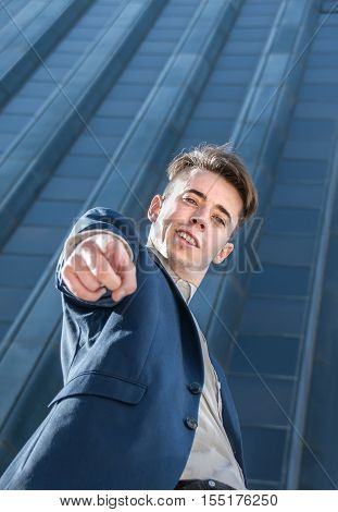 Successful business man pointing at camera over office building background