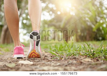 Rear Cropped View Of Woman Runner Wearing Pink Sneakers While Jogging Outdoors. Sole Of Female Runni