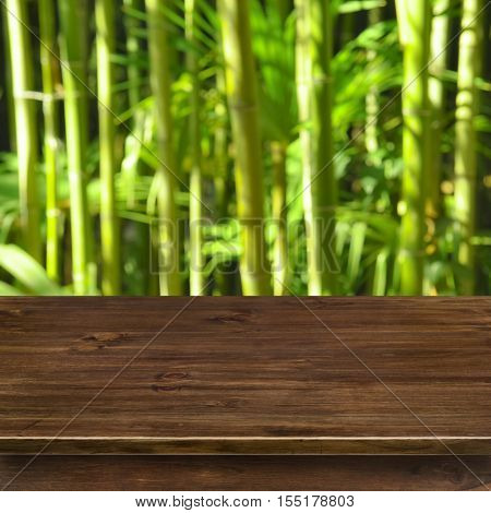 Green bamboo grove background with wooden table