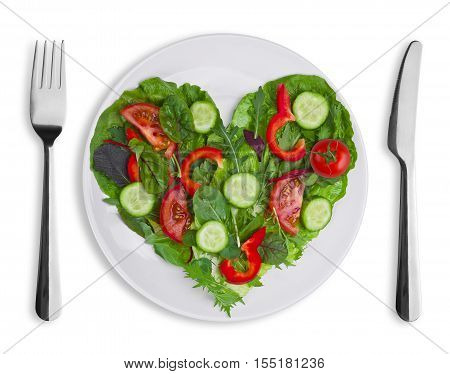 Heart shape of various vegetables and herbs on white plate