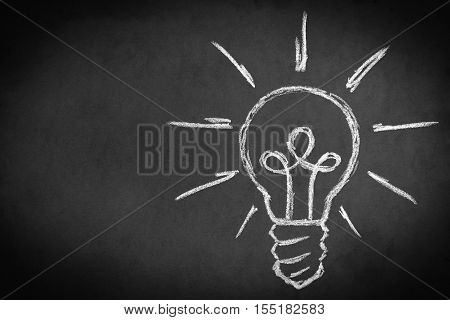 Light bulb chalk drawing on blackboard. Educational concept
