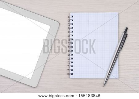 Modern tablet pc with note pad and pen on wooden desk