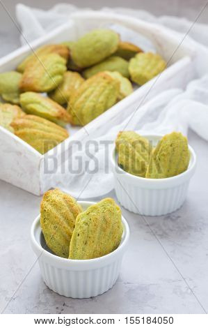 Homemade matcha green tea madeleines on the table and in wooden tray vertical