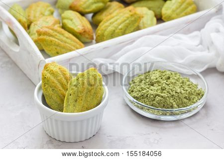 Homemade matcha green tea madeleines on the table and in wooden tray horizontal