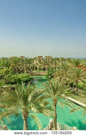 DUBAI, UAE - OCTOBER 14, 2016: A high level view of the lake in Al Qasr hotel set against green palm trees and a blue sky