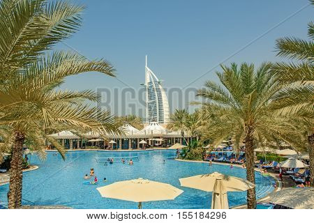 DUBAI, UAE - OCTOBER 14, 2016: A different view of the iconic Burj al Arab set against green palm trees and the swimming pool in Al Qasr Hotel
