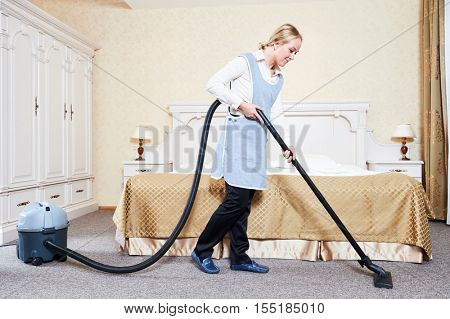 Hotel service. female housekeeping maid worker with vacuum cleaner in room apartment
