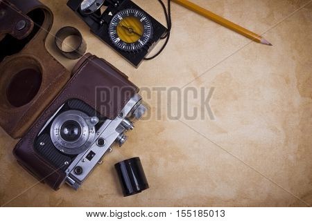 Old camera with filmstrip and compass on dark background