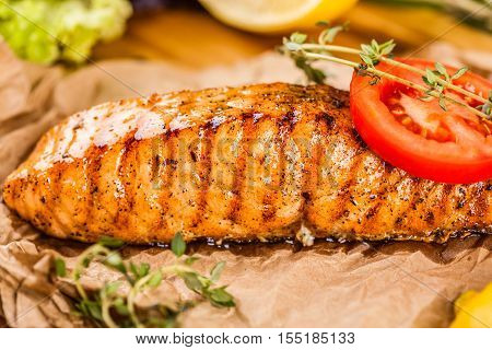 Grilled salmon with tomato slice on woden board