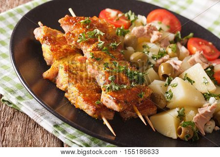 Spanish Food: Kebab Pinchos Morunos And Vegetables Salad Close-up. Horizontal