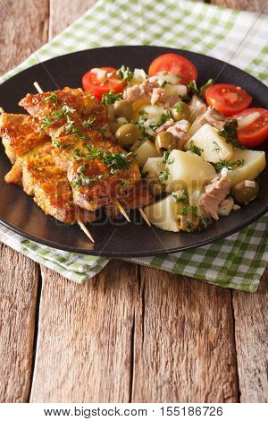 Spanish Food: Kebab Pinchos Morunos And Vegetables Salad Close-up. Vertical
