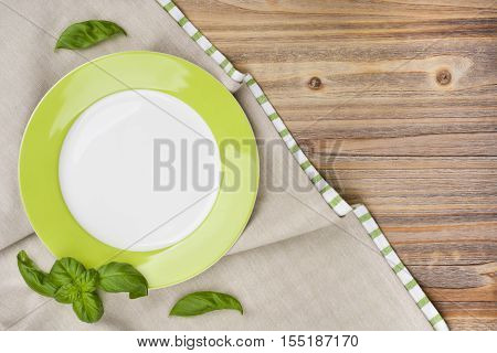 Plate with basil leaves on wooden table with tablecloth background
