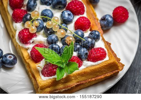 Waffels with cream and berry fruits on old wooden table