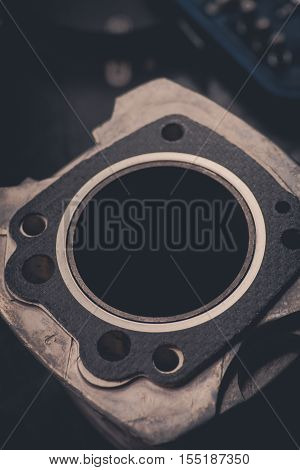Close up shot of a motorcycle's air-cooled cylinder and gasket.