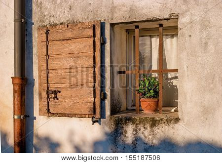 Old window with open shutters with flowers on the window sill on the stone wall. Italian Village. To the left of the window is the downspout.
