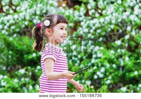 Cheerful little girl is a magician the flowered garden in summer