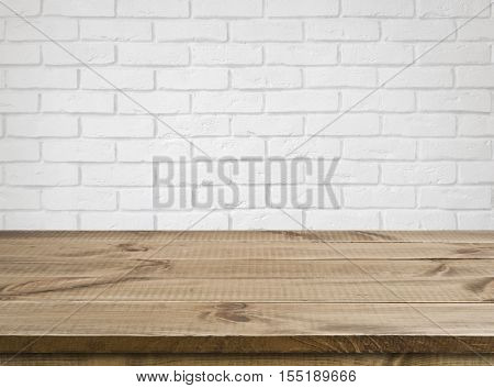 Rough wooden texture table over defocused white brick wall background