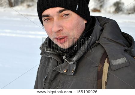 attractive adult man in the hat outdoor winter